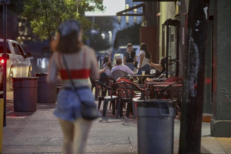 A woman walks by The Boot Bar and Grill while people mill around outside on Sept. 10. The Boot is the site of a recent sexual battery, in addition to the starting point of two recent sexual assaults. Photo credit: Andres Fuentes