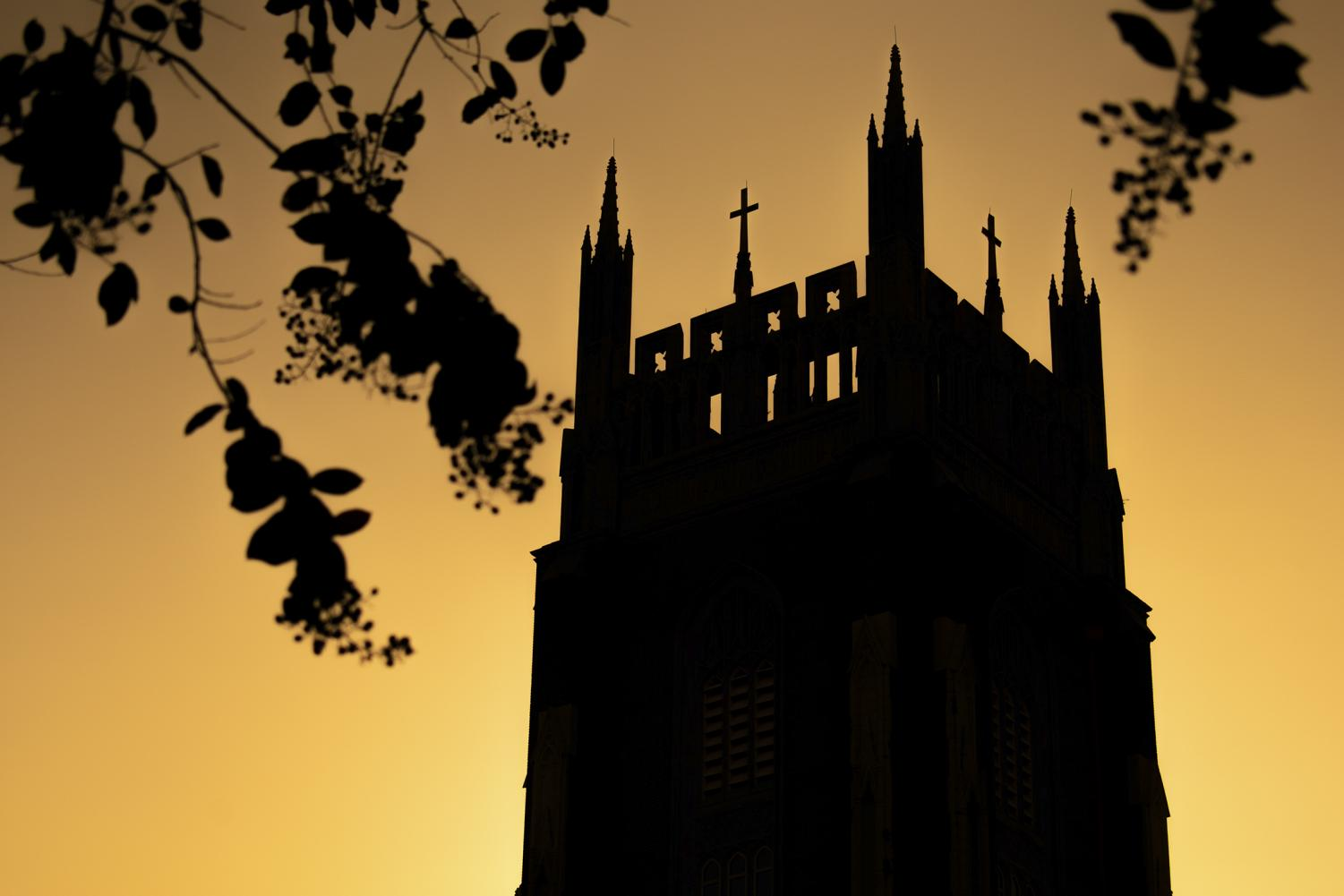 The sun sets on Holy Name of Jesus Church on Sept. 24, 2019. Loyola is undergoing the Mission Priority Examen to reevaluate its commitment to Jesuit values and traditions. Photo credit: Michael Bauer