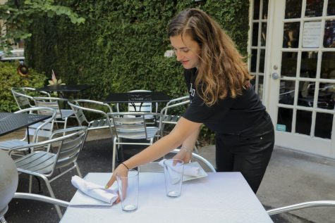 Mass Communications senior, Lili Mae Kinney, sets outside table for guests at Uptown restaurant Tito