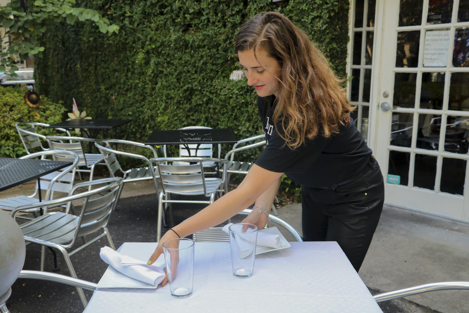 Mass Communications senior, Lili Mae Kinney, sets outside table for guests at Uptown restaurant Tito's Ceviche & Pisco. on Sept. 11, 2019. She has been working there since the summer of the same year.
