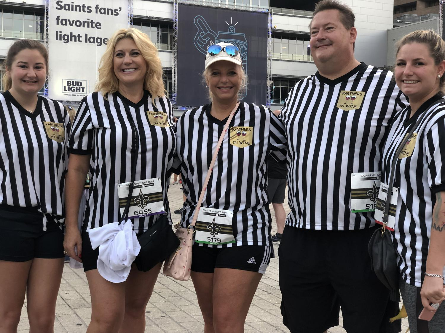 Jennifer Dutchover (center left) and Kim Koplin (center) pose with their family, dressed as referees at the Saints Kickoff Run on Sept. 7. Dutchover and Koplin traveled from Biloxi, Mississippi and Chicago, Illinois respectively, for the run. Sam Lucio/The Maroon Photo credit: Sam Lucio
