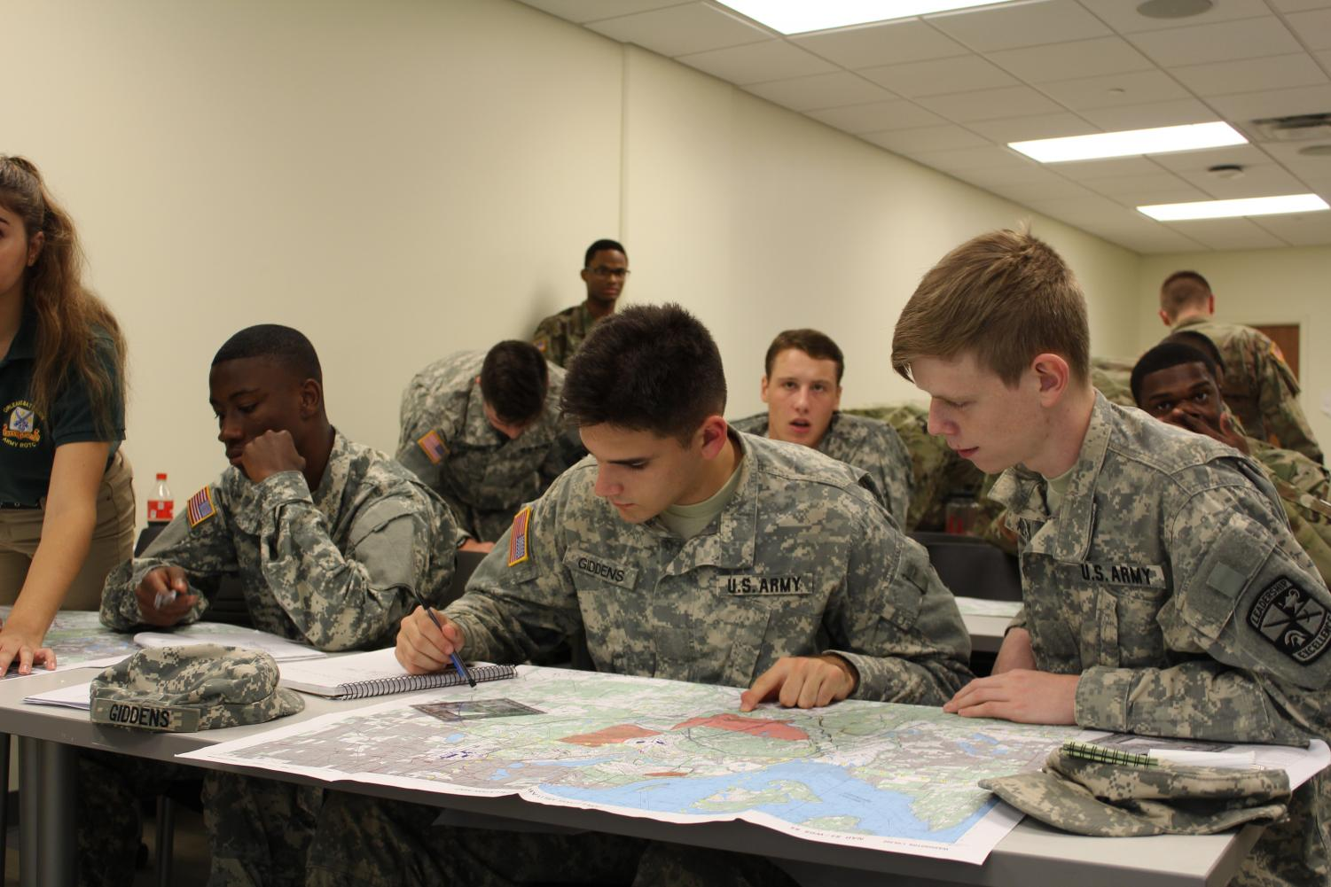 Ethan Giddens, psychological science freshman, plots points on a map in the land navigation lab on Tulane's campus. College students throughout the city travel to Tulane to participate in ROTC. Photo credit: Cristo Dulom