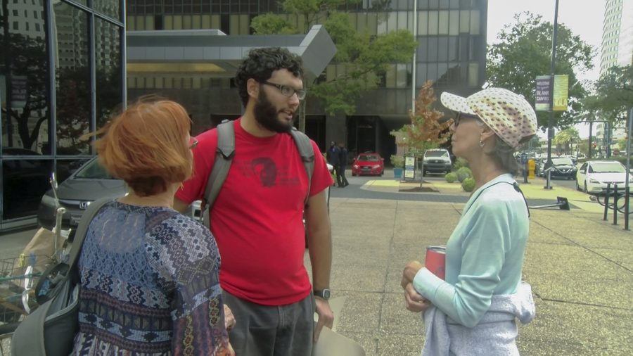 Daniel Werst speaks to other protesters in front of the ICE office in New Orleans Oct. 12. Werst said he supports an open border policy. Photo credit: Cody Downey