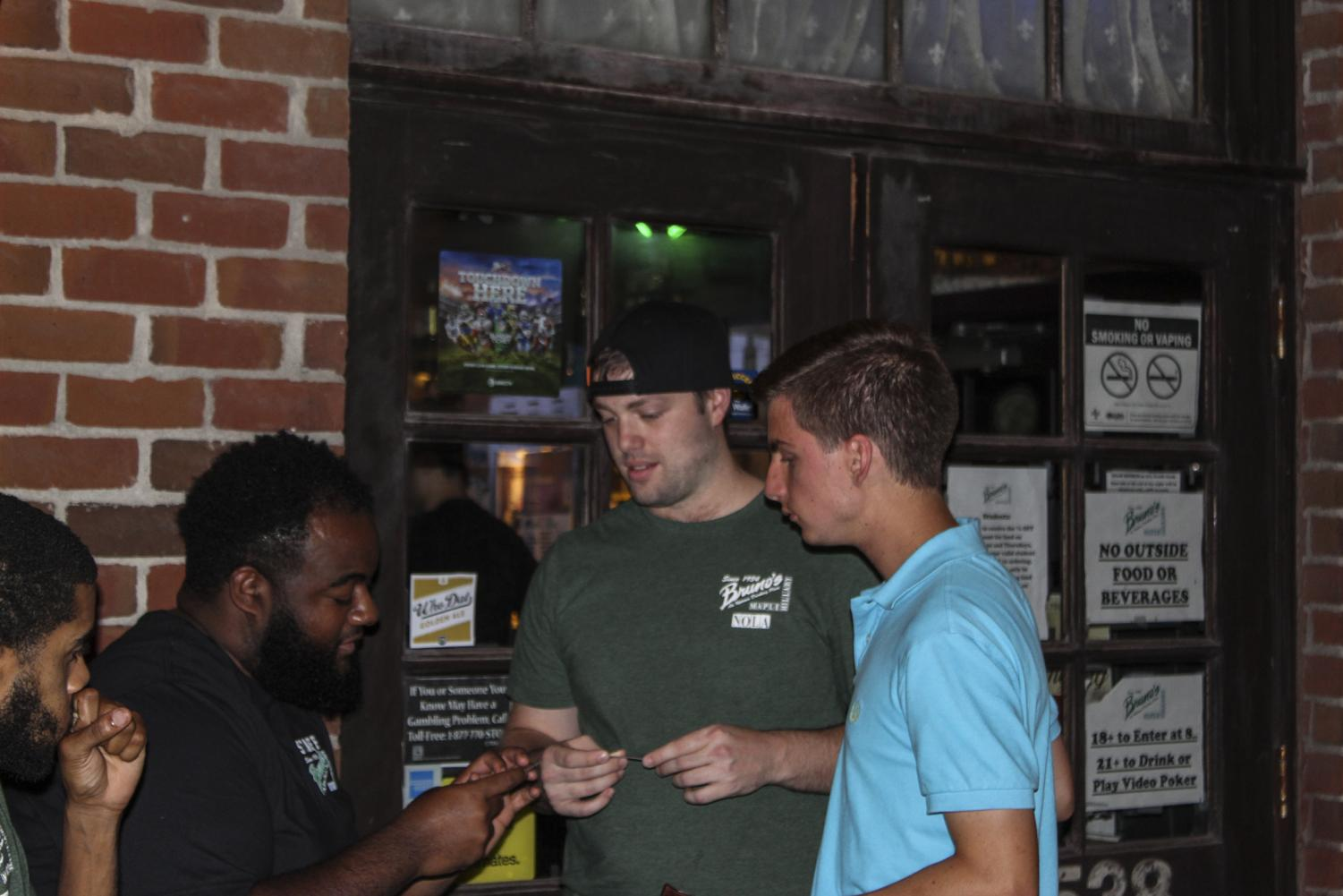 A Bruno's bartender checks students' IDs on Wine Wednesday on Oct. 4. Bruno's trains all bartenders and bouncers to be able to spot fake IDs.