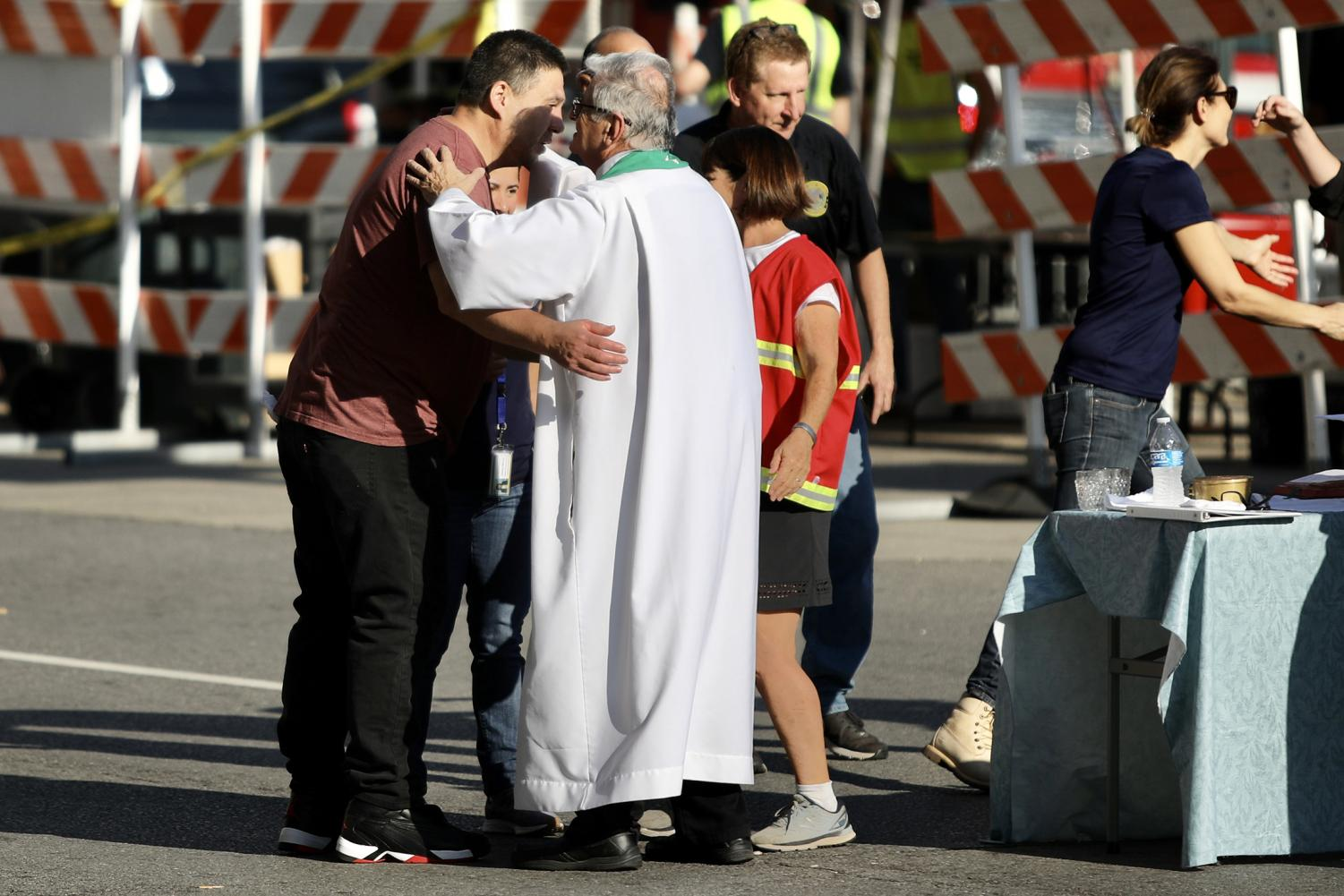 Sergio Ponce and the Rev. Anthony Rigoli come together for a hug following a mass just blocks away from the collapsed Hard Rock Hotel on Oct. 20, 2019. Ponce is the brother of one of the three construction workers that were killed in the collapse. Photo credit: Andres Fuentes