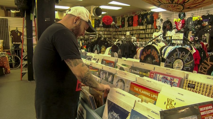 A+Mushroom+employee+shuffles+through+a+section+of+vinyl+records.+Mushroom+has+been+selling+vinyl+records+since+1969.+