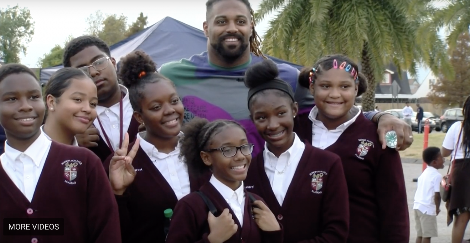 Cam Jordan posing with students. photo credit: Tess Rowland