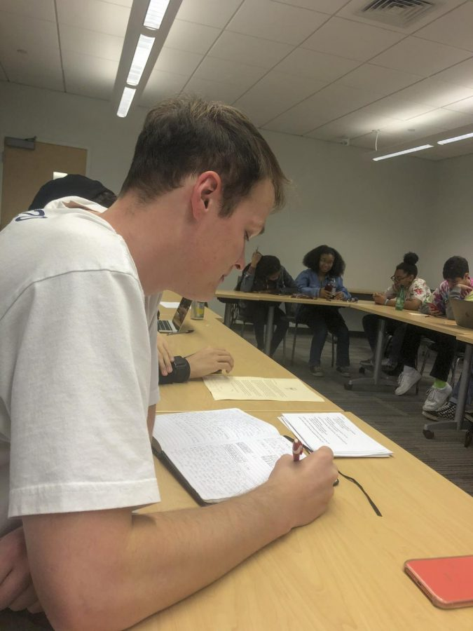 Caleb+Kinneman%2C+finance+freshman%2C+takes+notes+in+his+American+Empire+class.+Kinneman+uses+personal+anecdotes+of+his+time+in+the+Pacific+to+support+his+point+in+class+discussion.+Photo+credit%3A+Rae+Walberg