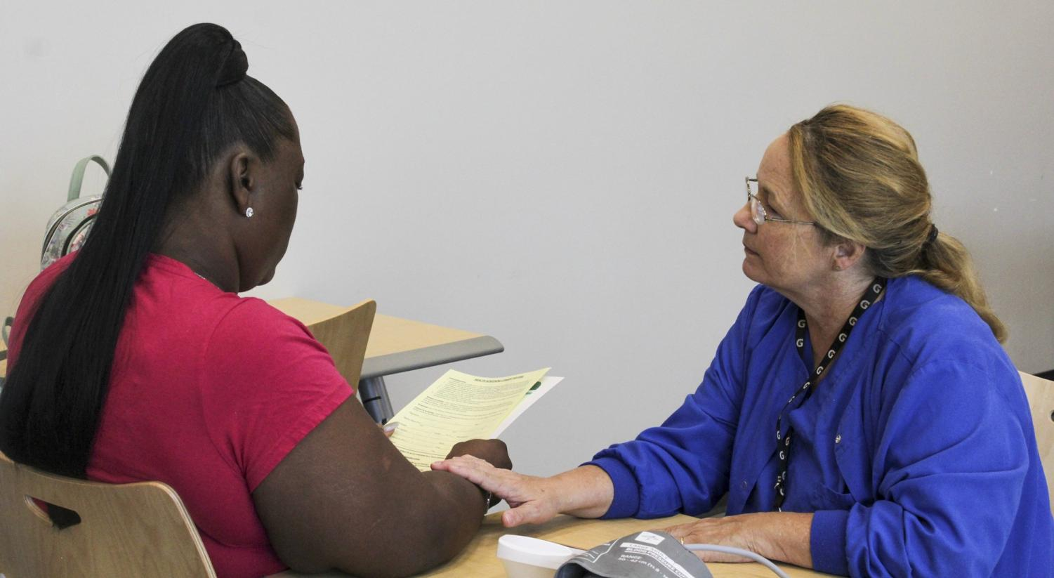 Registered nurse Kathe Haase (right) reviews Shannon Jackson's (left) paperwork with her following a blood pressure screenings. These screenings are provided for free to the public by the city and Touro as part of the Healthy Women New Orleans initiative. Photo credit: Shadera Moore