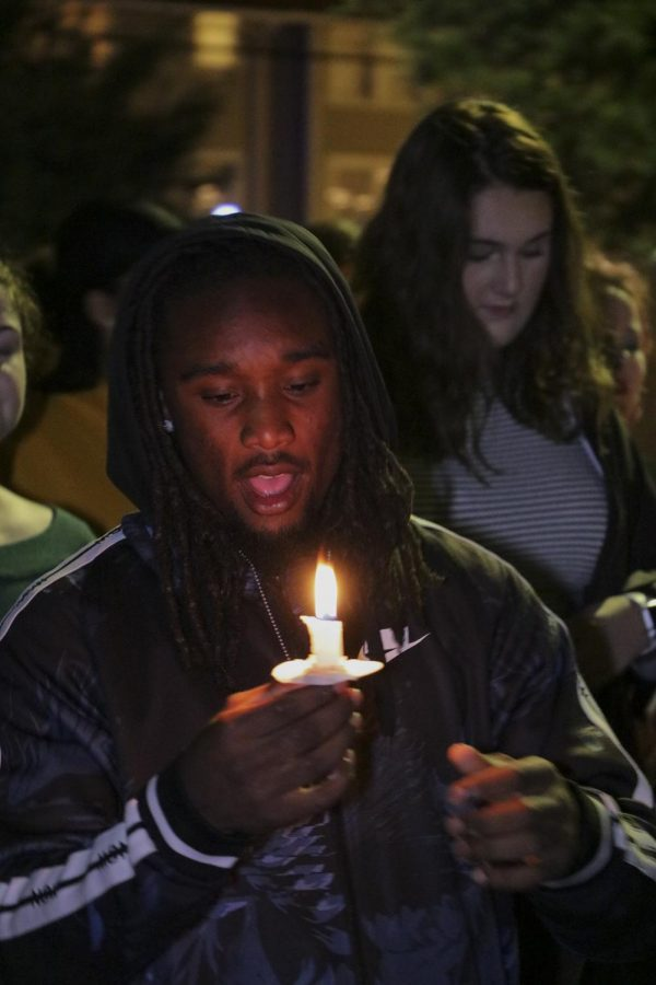 A Take Back the Night participant holds a candle while marching on Oct. 24, 2019.