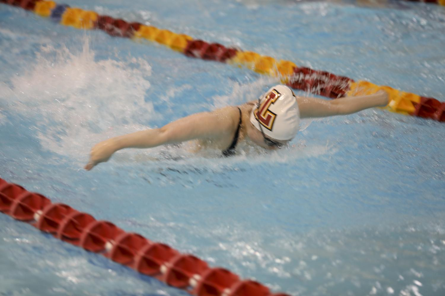 Loyola swimmer hits the pool in a meet.  The swim team holds practices at six in the morning every day except for Sunday. Photo credit: Andres Fuentes