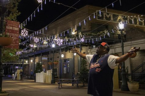 Pierre Wilbourn, a New Orleans resident, enjoys the light display as he awaits the snowfall on Fulton Street. Each year, thousands of people visit Miracle on Fulton Street to experience the faux snow and beautiful light display. Photo credit: Caitlyn Reisgen