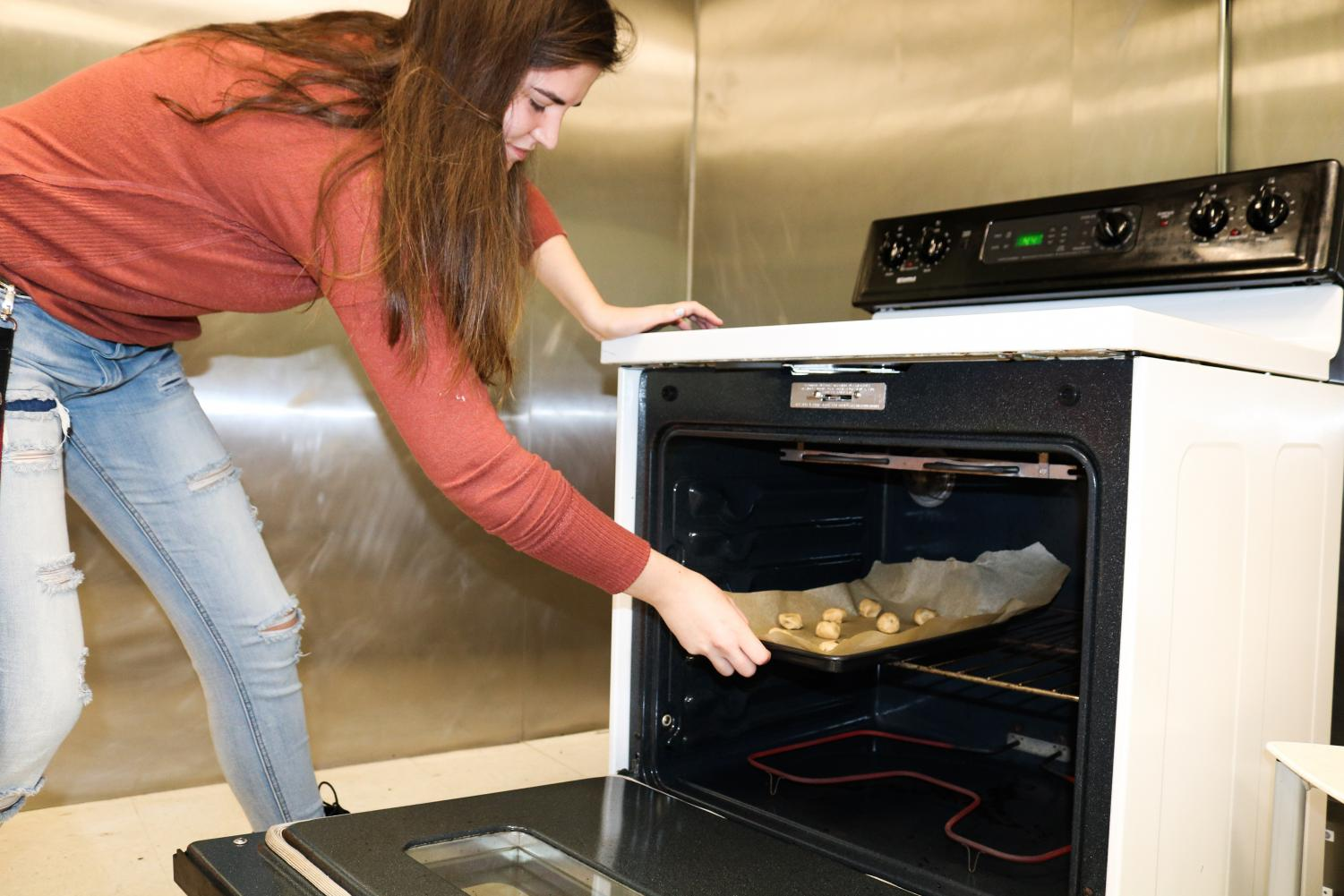Psychology sophomore Kylie Evans puts food in the oven in the Carrollton Lounge & Kitchen. The newly reopened space was converted from Deaux into a space for use by students. Photo credit: Zia Sampson
