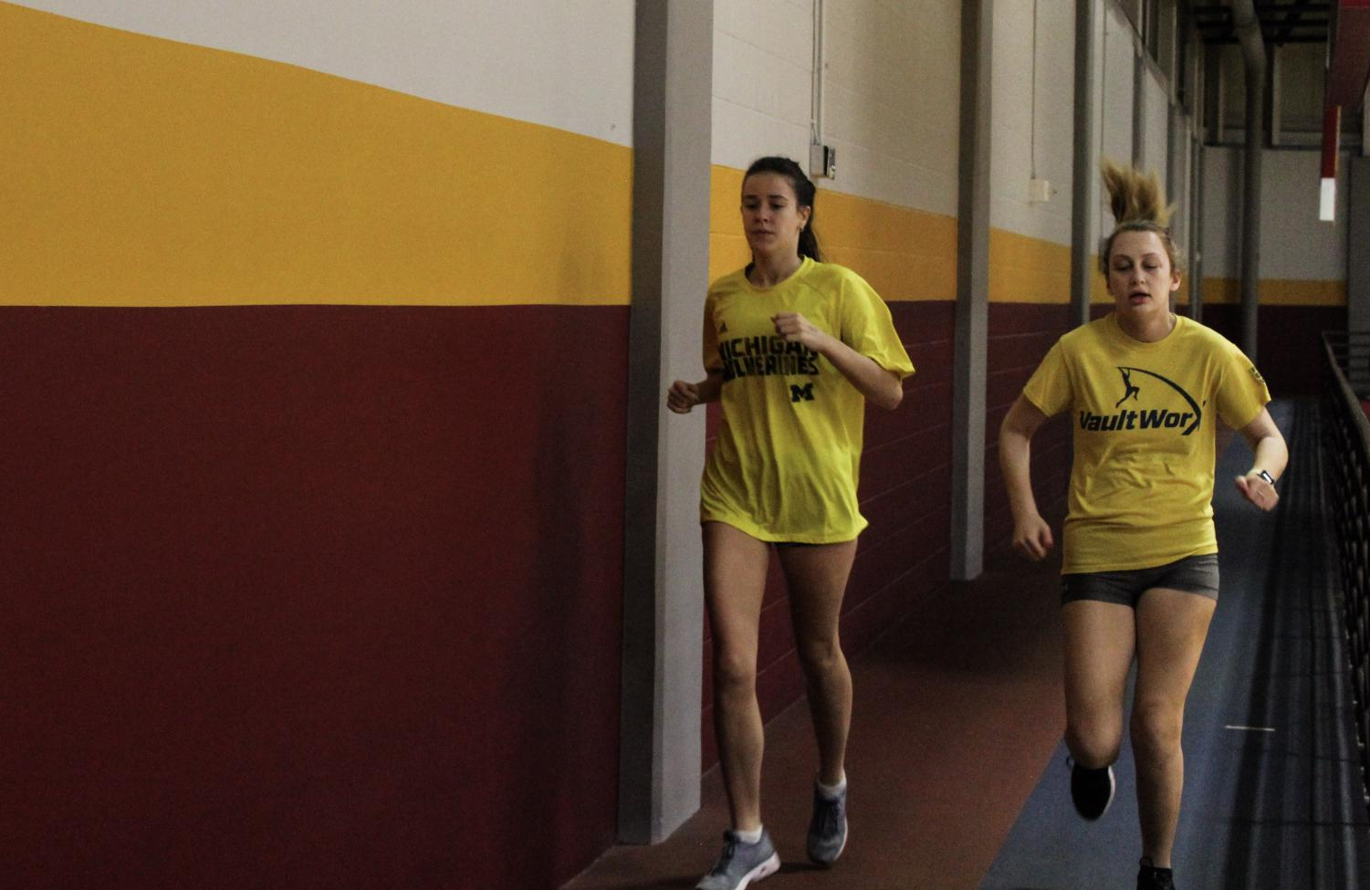 Mass Communication junior Ellen Harper (left) and freshman Mikaela Bradley (right) finish running a lap at track and field practice in the University Sports Complex on Friday, Jan. 10, 2020. The men's and women's teams are preparing for their next meet.