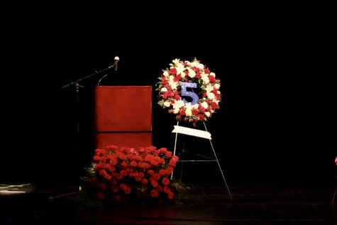 A flower display is arranged into the number 5 and sits next to a podium.
