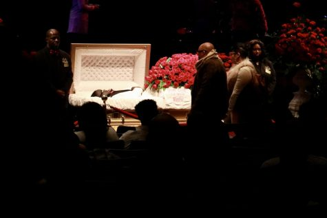 Mourners stand next to 5th Ward Weebie's casket at his funeral.