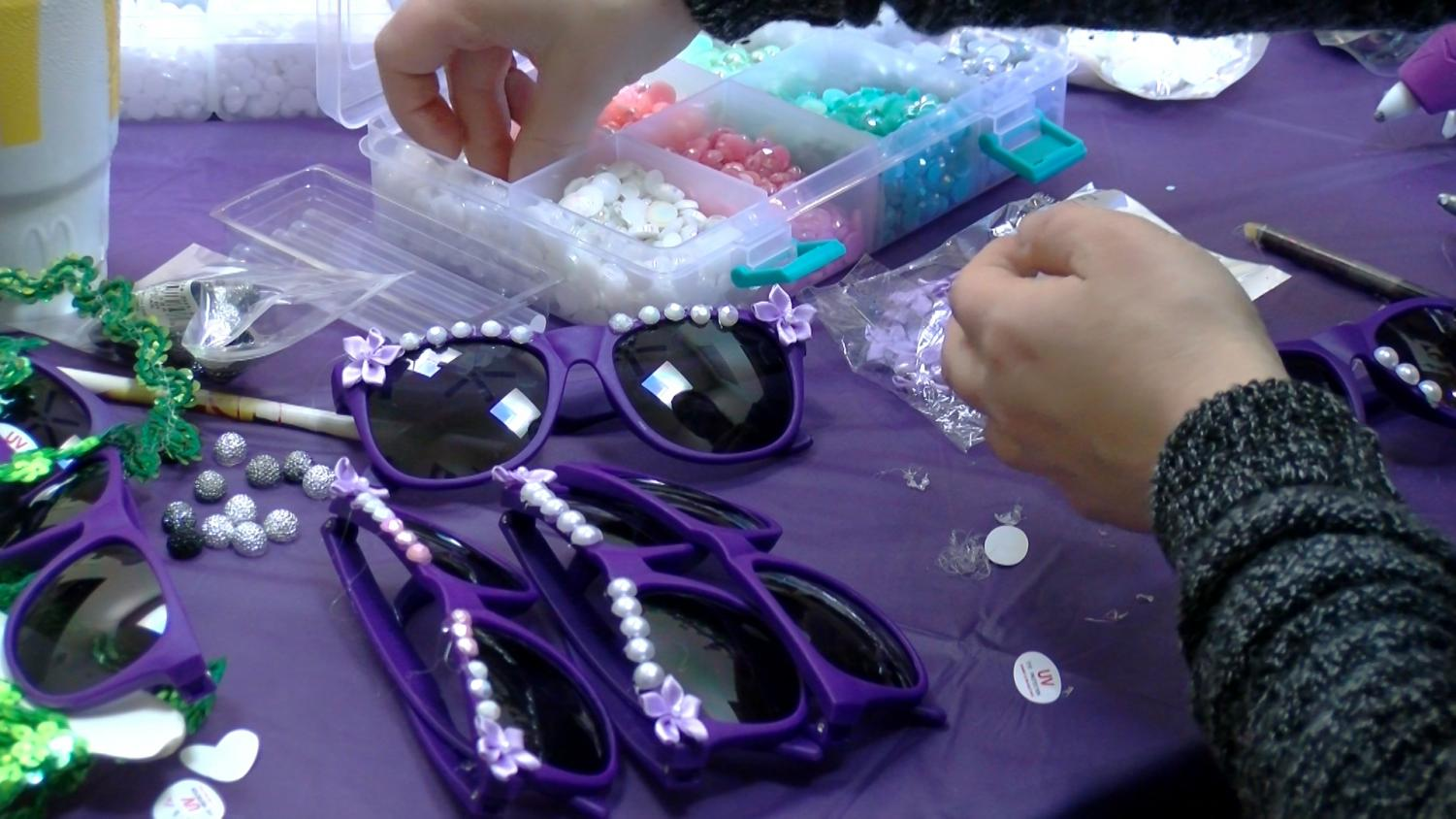 Members of the Krewe of Iris decorate their signature sunglasses. The all-female Krewe rolls Uptown the Saturday before Mardi Gras Photo credit: Amy Ngo