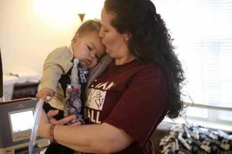 Andrea James and her son, Axel Dennis, embrace in their living room. Axel suffers from SMA and has twice been denied a life-saving drug from the Louisiana Department of Health. Photo credit: Andres Fuentes