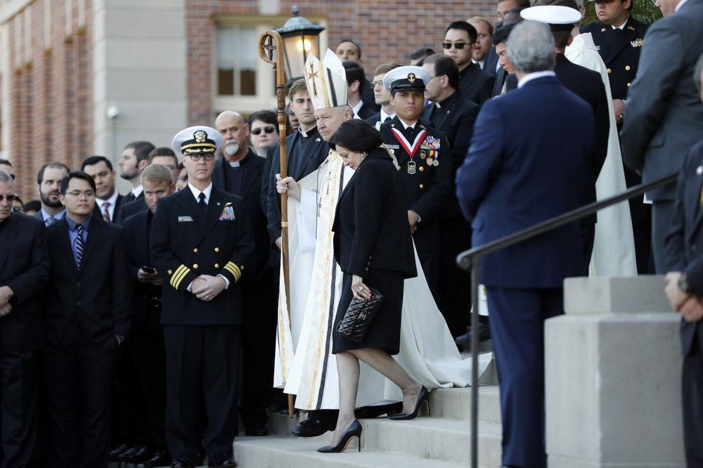 "In this March 21, 2018, file photo, Gayle Benson, widow of NFL New Orleans Saints and NBA New Orleans Pelicans owner Tom Benson, walks down the steps to receive his casket with New Orleans Archbishop Gregory Aymond for visitation at Notre Dame Seminary in New Orleans. Attorneys for several men suing the Roman Catholic church say documents they obtained through discovery show that the New Orleans Saints team aided the Archdiocese of New Orleans in its ""pattern and practice of concealing its crimes."""