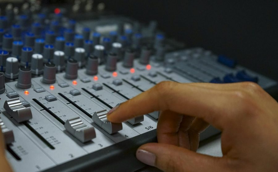 A student adjusts the volume dial on a mixer. The music industry college offers a mix of music and business classes for its students.