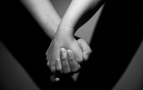 A black and white photo of two hands holding.
