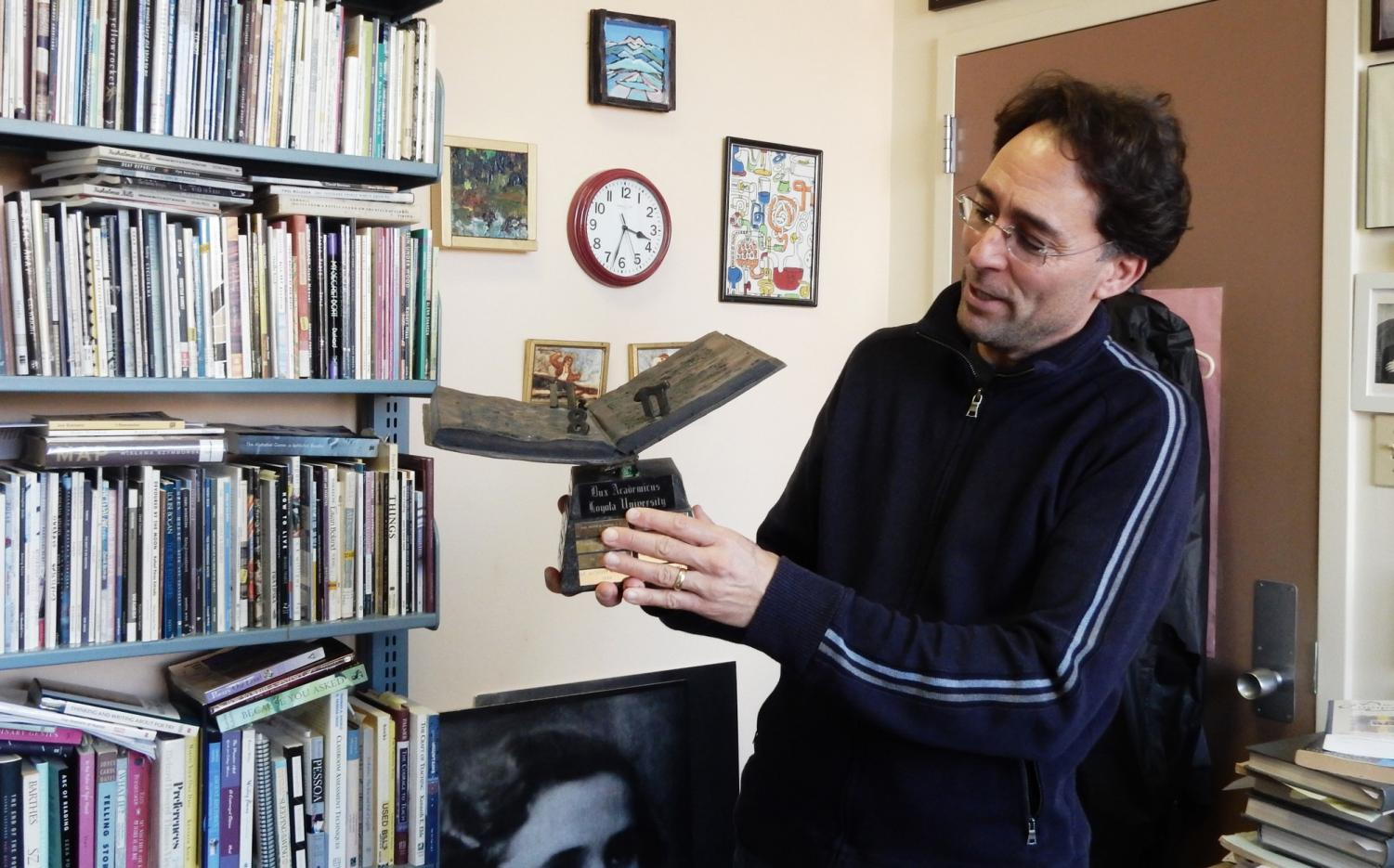 English professor and Dux Academicus Award winner Mark Yakich describes what his new trophy means to him. Pictured in his office on Jan. 23, 2020, he is surrounded by artwork from friends and books he enjoys as well as books he has written. Photo credit: Shadera Moore