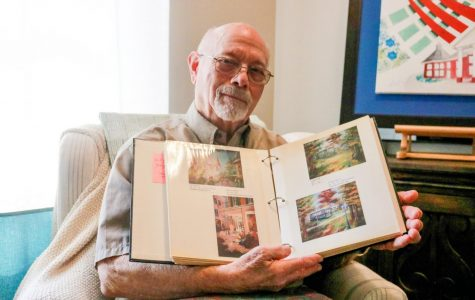 Norman Weinstein holding book of his paintings open.