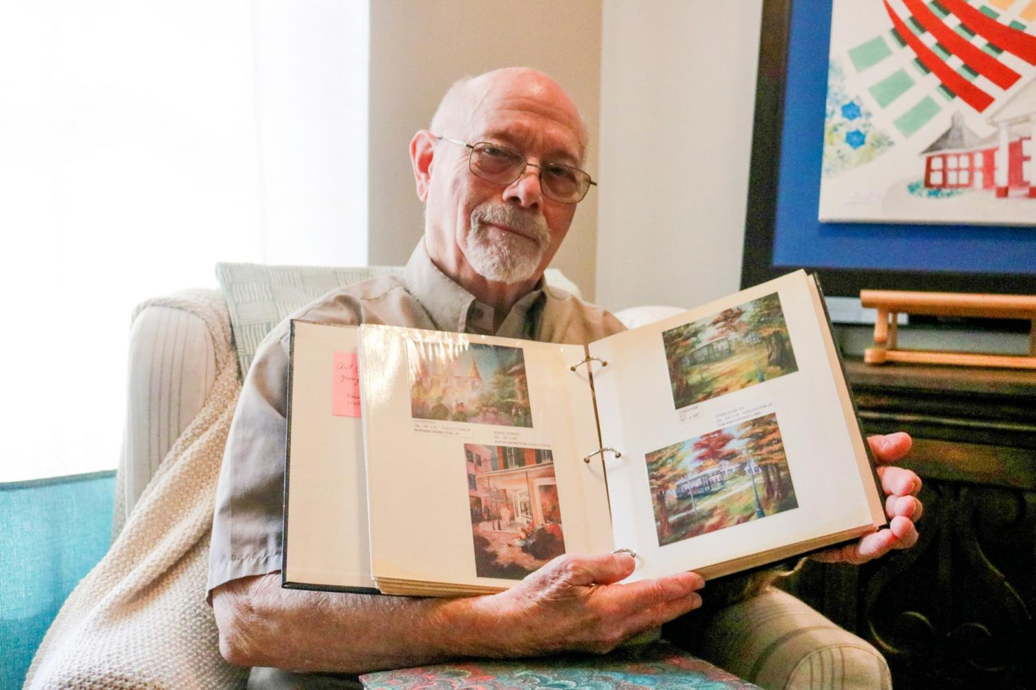 Norman Weinstein looks at scrapbooks filled with photos of paintings he has done over a span of 30 years.