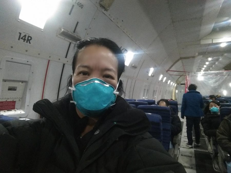 Loyola Law Professor Chunlin Leonhard sits on a plane out of China, her faced covered with a medical mask in the wake of the coronavirus outbreak.