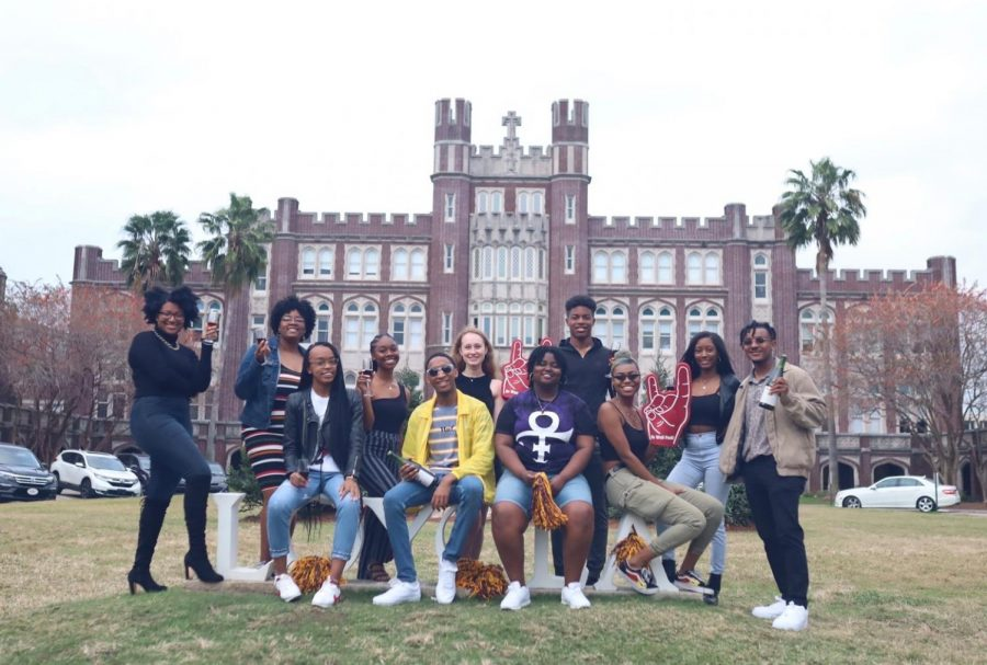 Students pose in front of Loyola's campus entrance.