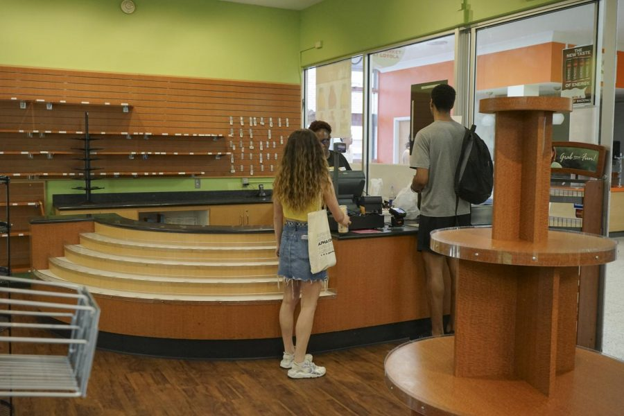 Two Loyola students buy some of the last items offered by the C-Store Market on March 13, 2020. After the announcement that classes were moving online, students quickly cleared out the C-Store Market. Photo credit: Cristian Orellana