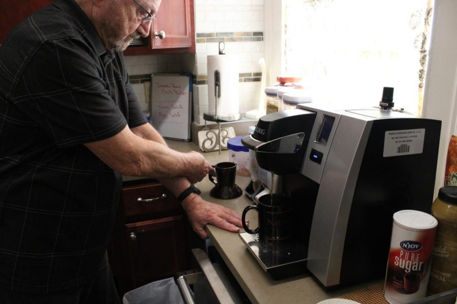 Father Carter prepares a drink in a kitchen
