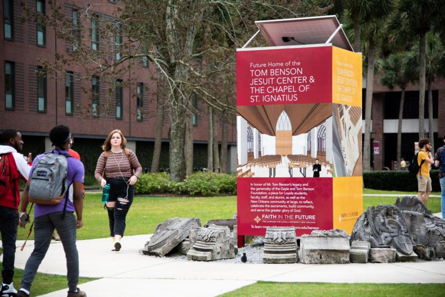 Students walk past the sign for the Tom Benson Jesuit Center in the center of campus on March 4. Loyola is relocating the plans for the center from the place where the sign sits to the corner of Monroe Hall near the large oak tree. Photo credit: Michael Bauer