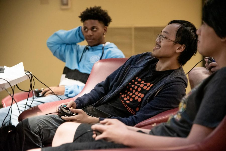 Gaming club President Quinton Liang (center)  plays Super Smash Bros in Satchmo's Lounge. E sports is a club sport at Loyola.  Mike Bauer \The Maroon