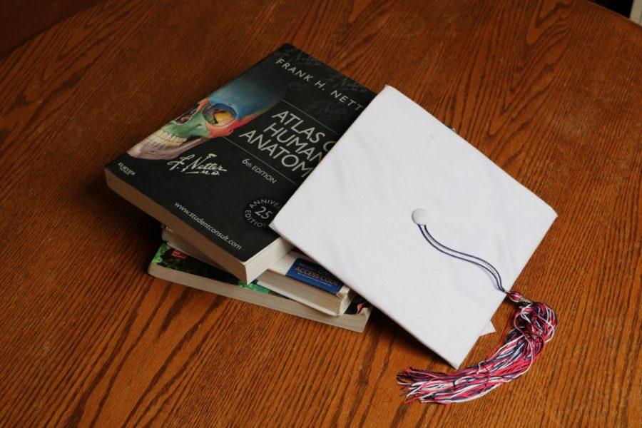 A+graduation+cap+sits+on+a+pile+of+graduate+school+books.