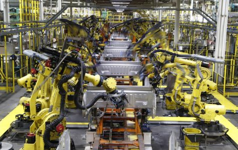 In this Sept. 27, 2018, file photo robots weld the bed of a 2018 Ford F-150 truck on the assembly line at the Ford Rouge assembly plant in Dearborn, Mich.  U.S. businesses are edging their way toward figuring out how to bring their employees back to work amid the coronavirus pandemic, a transition that some say will result in increased automation. (AP Photo/Carlos Osorio, File)