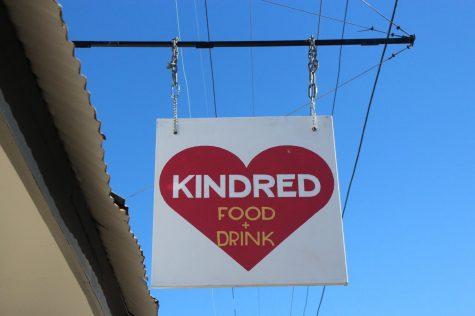 A business sign for Kindred, a New Orleans restaurant, hangs outside