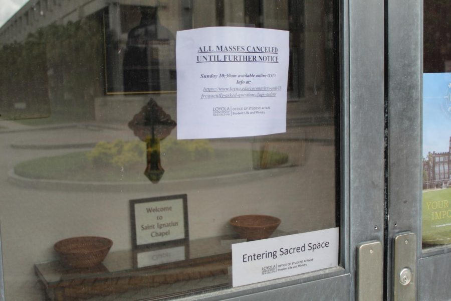 A sign on the door to Ignatius Chapel on Loyola's campus on May 17, 2020 references the closure of in-person worship services. The chapel re-opened on May 17 for in-person Sunday mass for the first time since the university's closure back in March. Photo credit: Alexandria Whitten