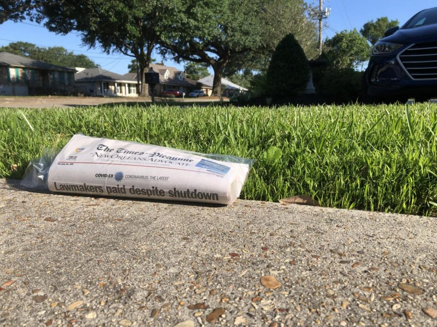 "An issue of The Times-Picayune | The New Orleans Advocate sits on a subscriber's driveway May 7. Due to COVID-19, local journalists have had their hours cut. The Advocate company put 10% of its staff on a ""permanent furlough,"" while the rest of the organization's staff members have had their hours cut for payroll savings, working four-day work weeks once every pay period, according to newsroom leaders. Photo credit: Michael Giusti"
