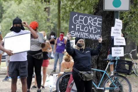 "A protester holds a sign that reads ""Goerge Floyd, say his name"""