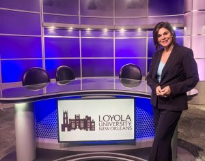 Sonya Duhé poses in front of the anchor desk in Studio A at Loyola.