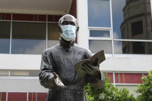 The statue of St. Ignatius of Loyola wears a protective face mask in the Peace Quad on Loyola's campus June 2020. While cases of COVID-19 are rising in Louisiana, Loyola still plans on reopening campus for in-person classes in August.