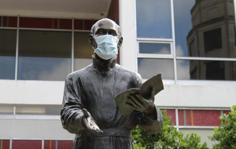 The statue of St. Ignatius of Loyola wears a protective face mask in the Peace Quad on Loyola's campus June 2020.