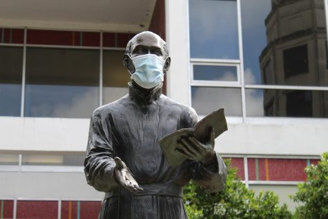 The statue of St. Ignatius of Loyola wears a protective face mask in the Peace Quad on Loyola