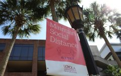 A sign promoting social distancing hangs from a lamppost in Palm Court Aug. 3. Loyola is offering free on-campus testing in an effort to prevent the spread of COVID-19. Photo credit: Alexandria Whitten