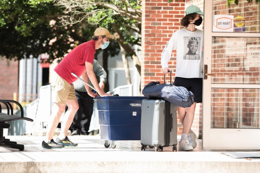 A student and parent enter Biever Hall with items for moving in on Thursday, August 20. Individuals in on-campus public spaces, including during move-in, are required to maintain a distance of 6 feet apart from one another and wear masks.