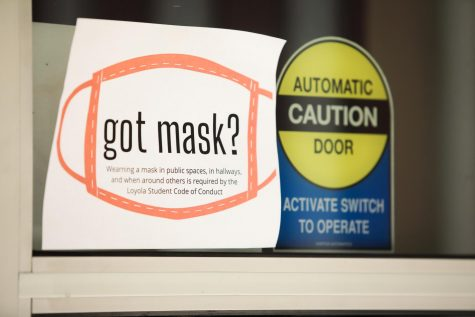 A sign with instructions to wear a mask while in on-campus public spaces hangs on a front door to Biever Hall on Thursday, August 20. The university has installed signage across campus with information related to COVID-19 policies.