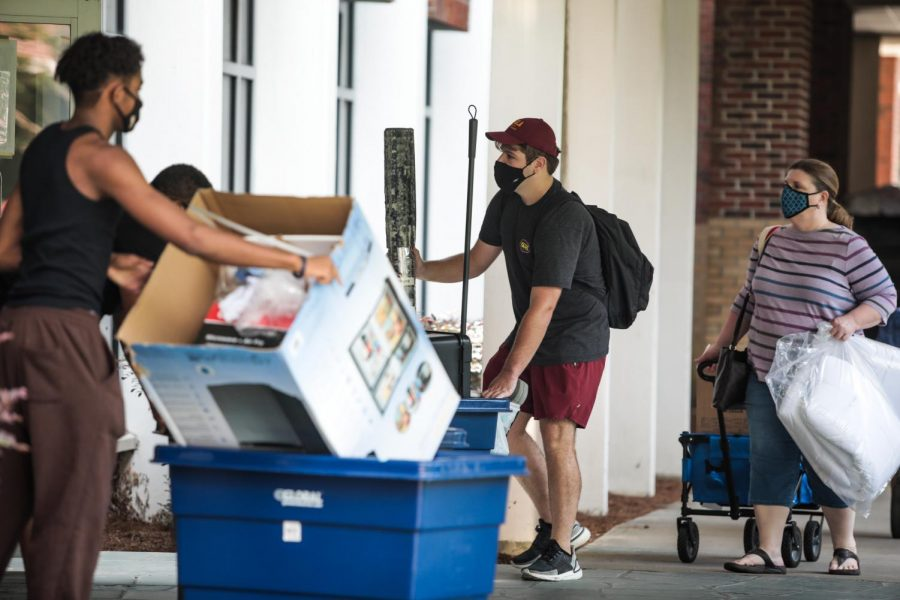 Students and parents pass through the Buddig Hall doors on Thursday, August 20. The residence halls now feature additional health and safety measures, such as sheets of plexiglass on the front desks.