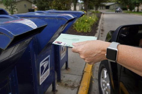 FILE - In this Tuesday, Aug. 18, 2020, file photo, a person drops applications for mail-in-ballots into a mail box in Omaha, Neb. U.S. Postal Service warnings that it can't guarantee ballots sent by mail will arrive on time have put a spotlight on the narrow timeframes most states allow to request and return those ballots. (AP Photo/Nati Harnik, File) Photo credit: Associated Press