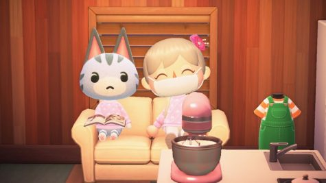 A screenshot from Animal Crossing shows two characters sitting on a couch